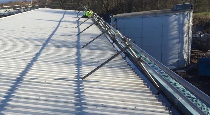 Giromax expert applying basecoat along roof sheet edges.