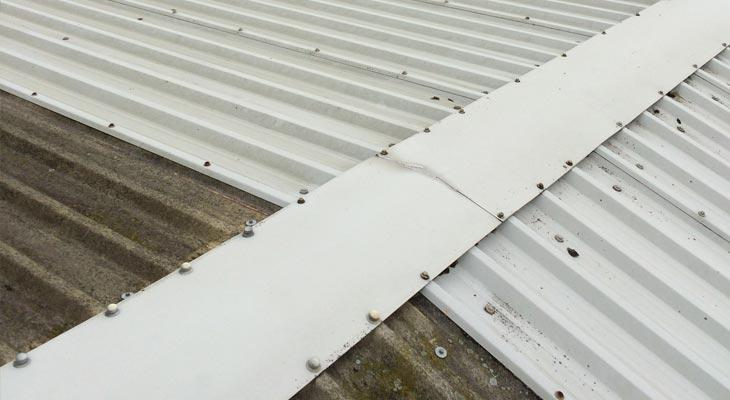 Ridge flashing with missing crown corrugation fixings.
