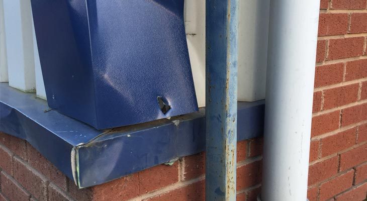 Close up of damaged corner flashing and base sill