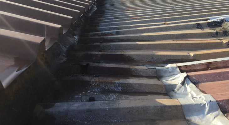Blocked valley gutter causing severe roof sheet delamination