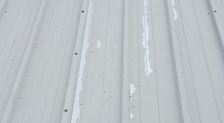 Industrial roofing jet wash reveals delaminating offset white plastisol