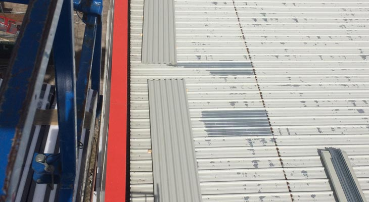 Industrial roofing jet washing exposing spotted delamination