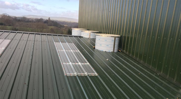 Three cylinder shaped flu stacks protruding from roof cladding