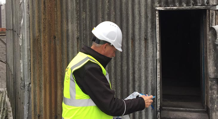 Coverclad manager inspecting non-notifiable asbestos wall cladding