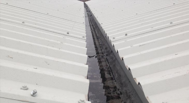 Eaves level view of asbestos roofing overclad