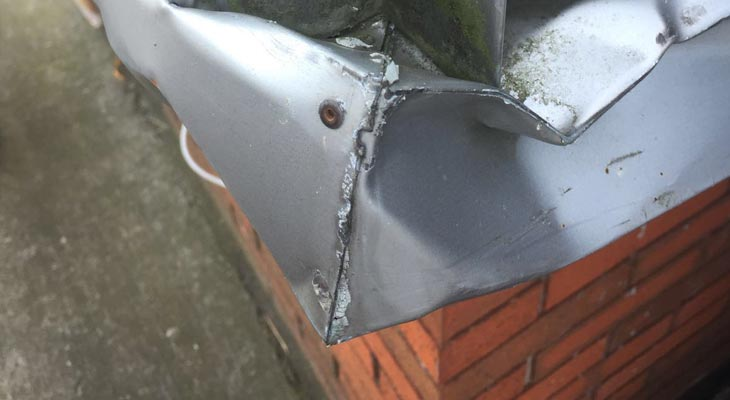 Close-up of vehicle impact damage to wall cladding base flashing