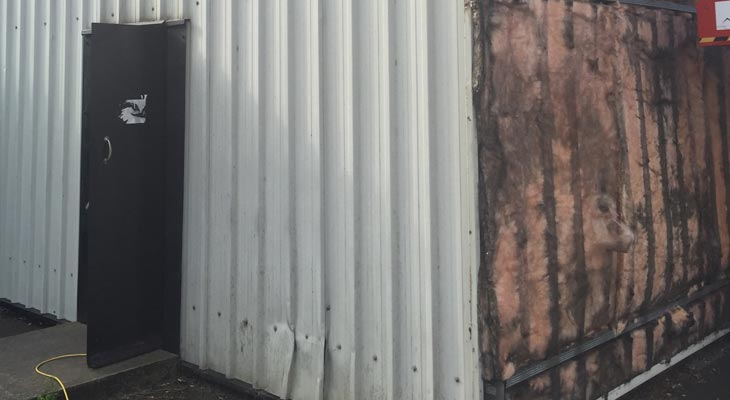 Wall cladding sheets removed exposing underlying insulation