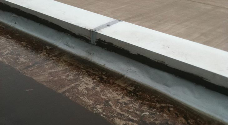 Failing historic repair to a parapet capping joint