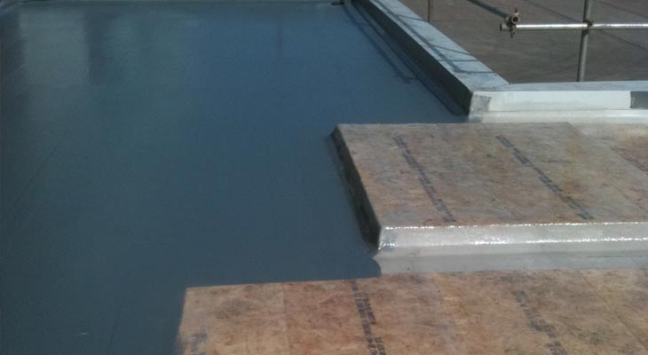 Glass reinforced plastic being applied in sections across flat roof