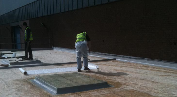 GRP roofing installer rolling out fleece during the resin stage