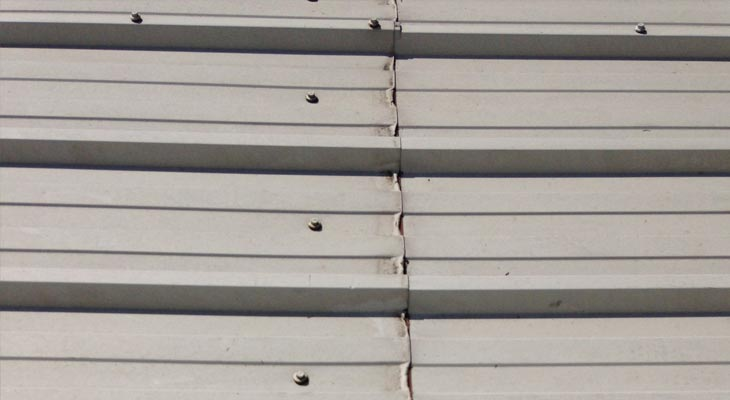 Cut edge corrosion to industrial roofing mid-laps