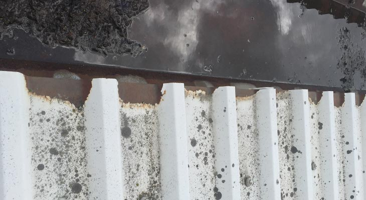 Close-up showing extensive cut edge corrosion to roof sheet eaves