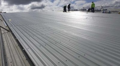 Coverclad operatives fixing down roof sheets