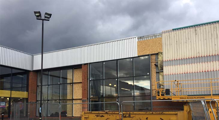 Installing wall cladding above glazing sections