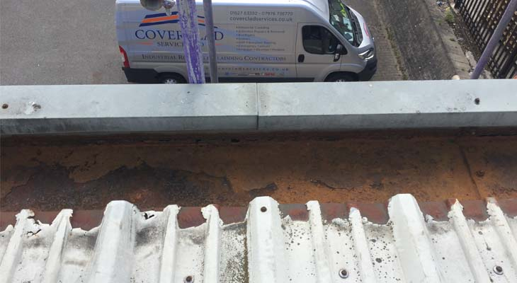 Cut edge corrosion and heavily corroded gutter with Coverclad van in the background