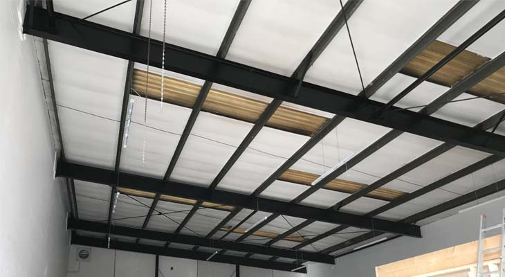 Internal view of old degraded roof lights impeding sunlight into warehouse
