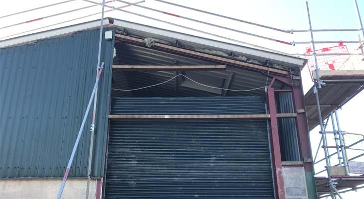 Gable end cladding stripped for roller shutter door height adjustment