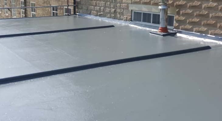 Dark grey GRP top coat rolled out across new flat roof