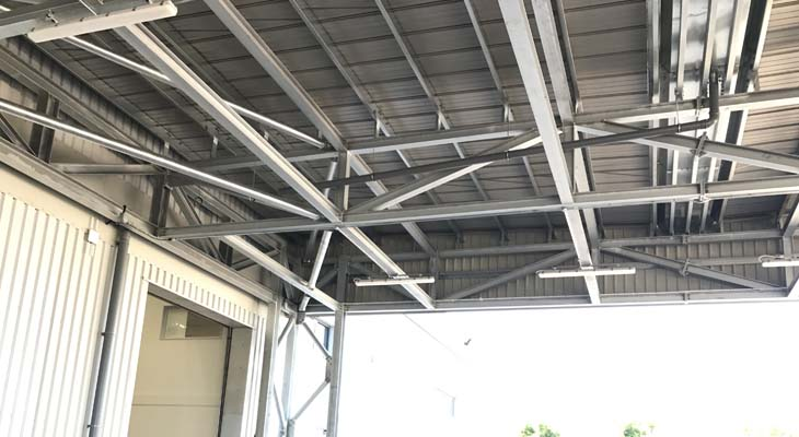 View of canopy underside with downpipe discharging from valley gutter